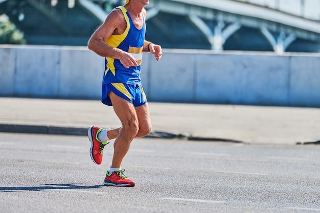 Correndo velho. velho correndo com roupas esportivas na estrada da cidade