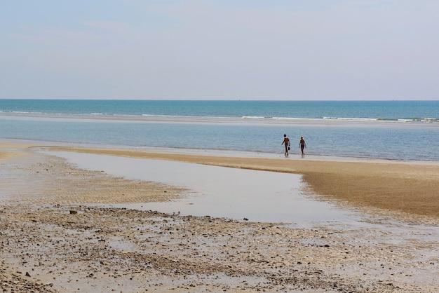 Corrente de água das marés na praia com o céu azul de manhã