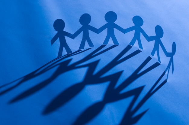 Corrente de homem de papel de mãos dadas em azul. símbolo de unidade, fraternidade e trabalho em equipe