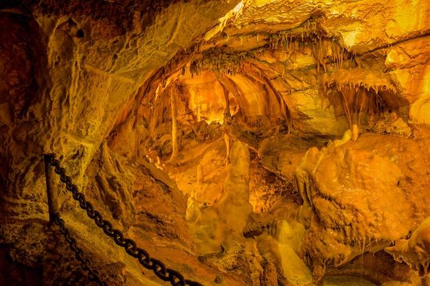 Corrente de metal pesado em cavernas da moeda com estalactites e estalagmites.