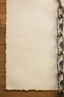 Corrente e papel antigo vintage velho em fundo de madeira