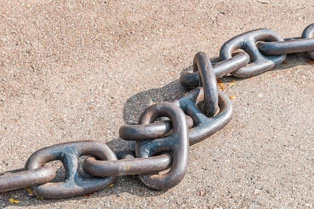 Corrente para a âncora do ferro pesado do metal em um fundo cinzento com uma sombra. fechar-se.
