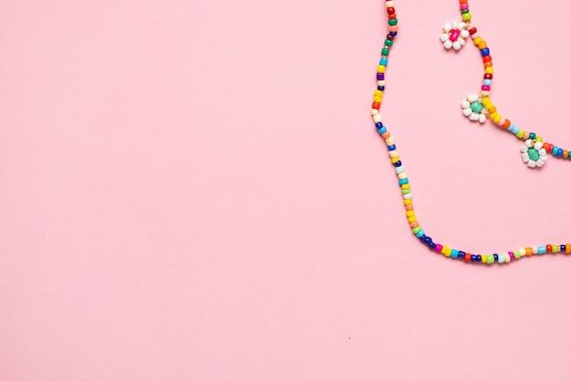 Corrente variada de miçangas para cintura com miçangas perler no fundo rosa, perfeita para as crianças usarem a vista de cima copyspace