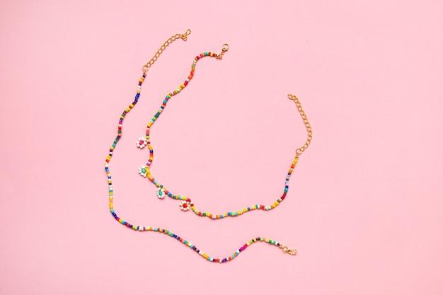 Corrente variada de miçangas para cintura com miçangas perler no fundo rosa, perfeita para crianças usarem a vista de cima
