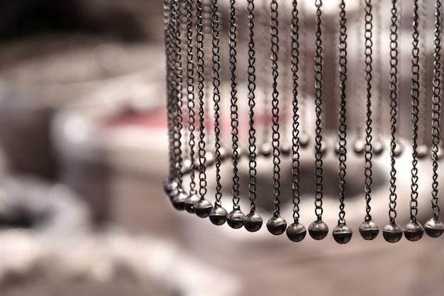 Correntes com sinos pendurar em um círculo sobre o fundo de sacos de especiarias.
