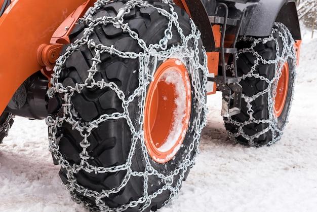 Correntes de metal para neve enroladas em pneus de roda de carro de escavadeira estacionado em estrada com neve