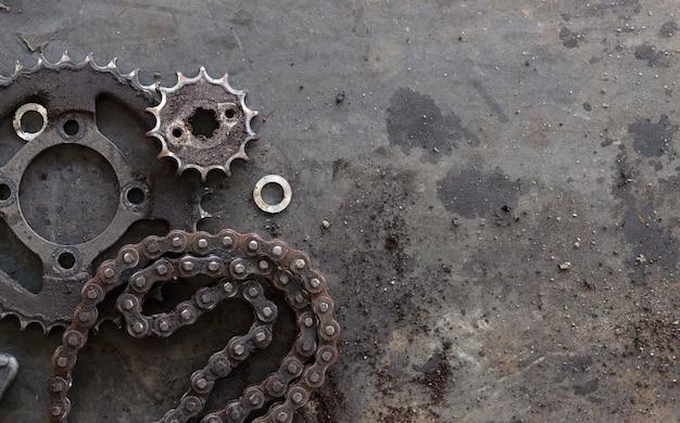 Correntes de rolo com rodas dentadas para motos em fundo preto velho. vista do topo