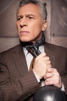 Correntes em seu pescoço. homem sênior de cabelos grisalhos em traje formal tentando tirar a corrente do pescoço