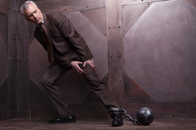 Correntes em sua perna. homem sênior de cabelos grisalhos de comprimento total em trajes formais tentando ir com as algemas da perna