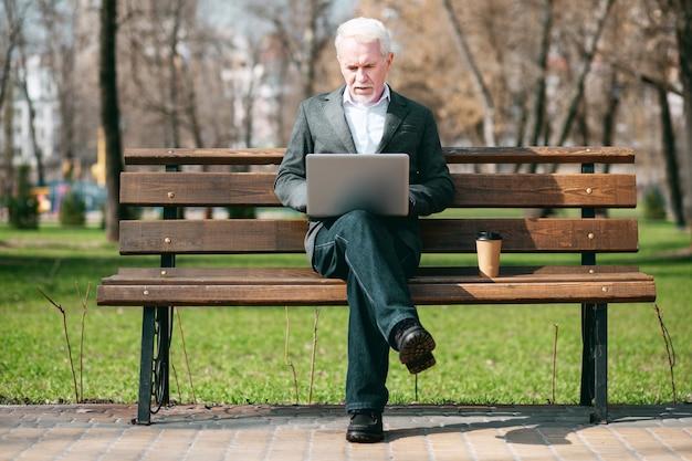 Correspondência de negócios. focado empresário maduro usando laptop enquanto está sentado no parque