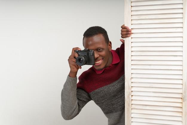Correspondente homem bonito preto tirando fotos de uma cena picante, ele faz notícias intrigantes, que ainda não são conhecidas por ninguém