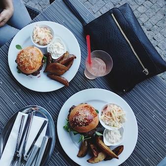 Corretamente namorar uma senhora com hambúrgueres suculentos e batatas assadas