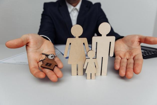 Corretor com chaves de casa, figuras de madeira de uma família à frente de hipoteca e conceito de compra