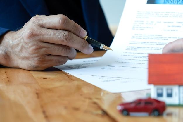 Corretor da casa segura caneta apontando para o documento.