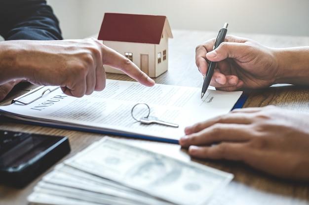 Corretor de agente imobiliário chegar ao formulário de contrato para o cliente assinar contrato contrato imobiliário com formulário de pedido de hipoteca aprovado