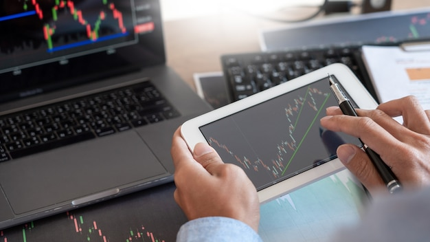 Corretor de empresário analisando gráficos e relatórios de dados financeiros na tela
