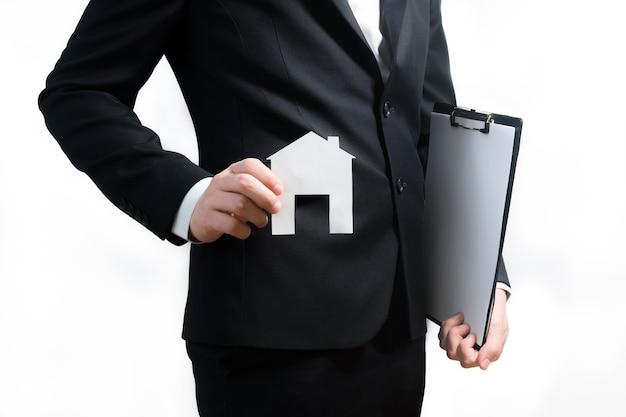 Corretor de imóveis, agente imobiliário segurando o tablet e o modelo de papel de uma casa.
