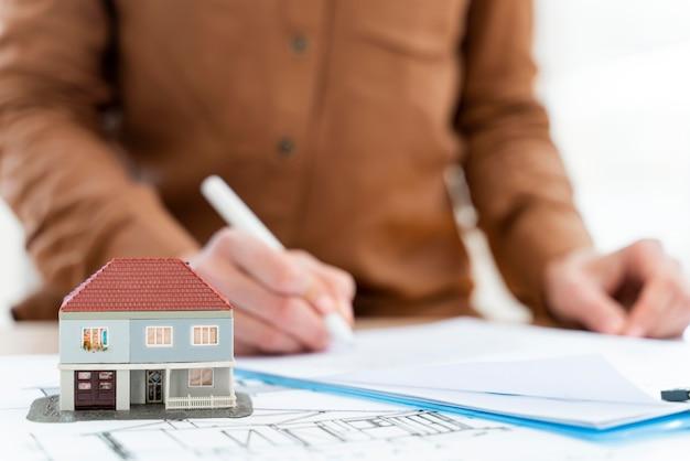 Corretor de imóveis assinando contrato na prancheta ao lado da casa em miniatura