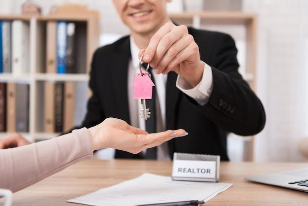 Corretor de imóveis dá chaves de mulher com chaveiro-de-rosa.