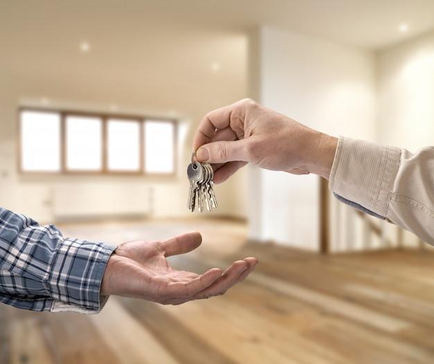 Corretor de imóveis, dando a chave da casa para o comprador no quarto vazio