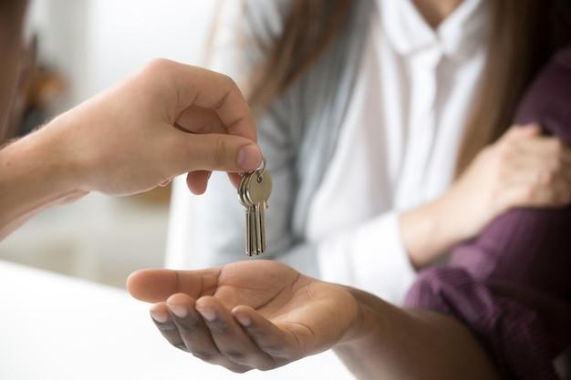 Corretor de imóveis dando chaves de clientes africanos, casal comprar casa nova, close up
