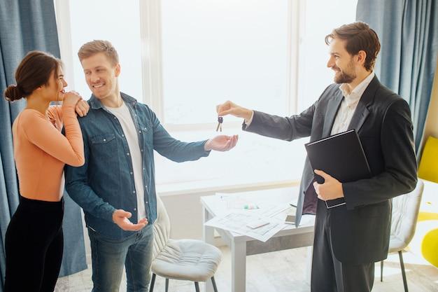 Corretor de imóveis dando chaves para casal