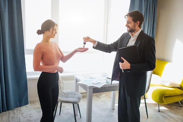 Corretor de imóveis dando chaves para mulher