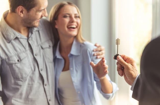 Corretor de imóveis de terno clássico está dando a chave para o novo apartamento.