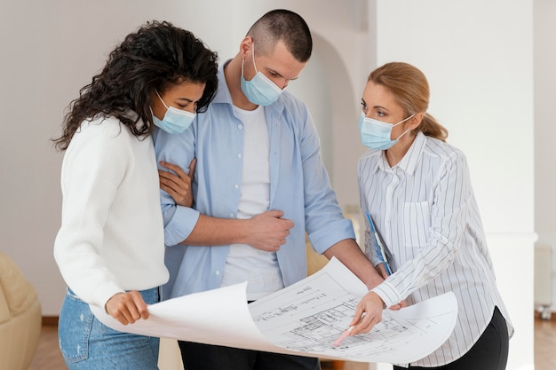Corretor de imóveis e casal com máscaras médicas olhando as plantas da casa