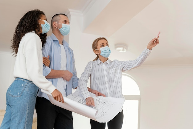 Corretor de imóveis e casal com máscaras médicas segurando plantas de casas