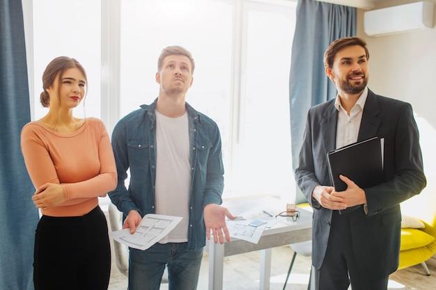 Corretor de imóveis e casal segurando blueprint