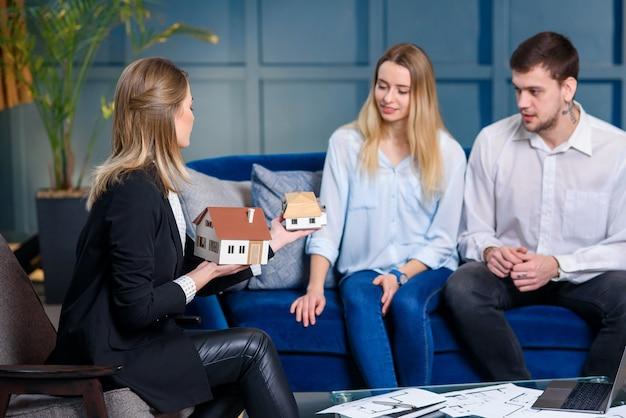 Corretor de imóveis elegante jovem, designer de interiores, decorador, conversando com dois clientes.