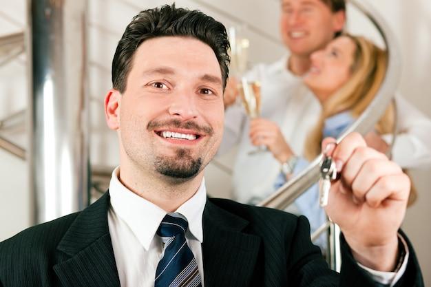 Corretor de imóveis em apartamento dando chaves para casal