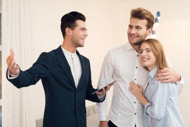 Corretor de imóveis em um terno mostra um novo apartamento para os clientes.