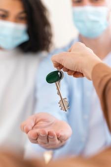 Corretor de imóveis entregando casal com máscaras médicas as chaves de sua nova casa