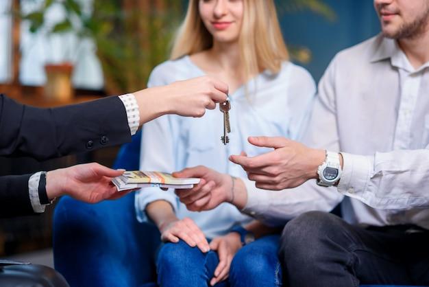 Corretor de imóveis feminino, dando a chave do apartamento, casa para o jovem casal enquanto cliente masculino dando dinheiro.