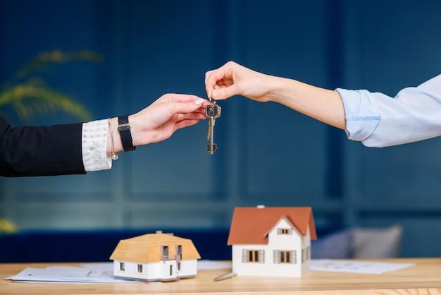 Corretor de imóveis feminino, dando a chave do novo apartamento, casa para clientes do sexo feminino.