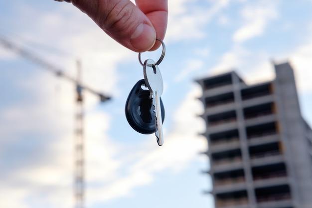 Corretor de imóveis homem, oferecendo as chaves da casa nova