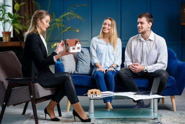 Corretor de imóveis jovem, designer de interiores, decorador na reunião com os clientes.
