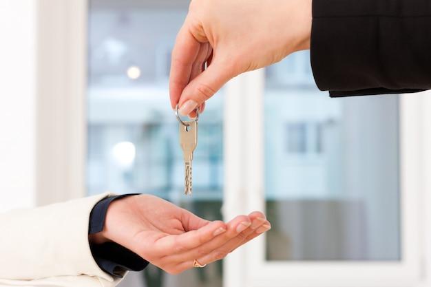Corretor de imóveis jovem é com chaves em um apartamento
