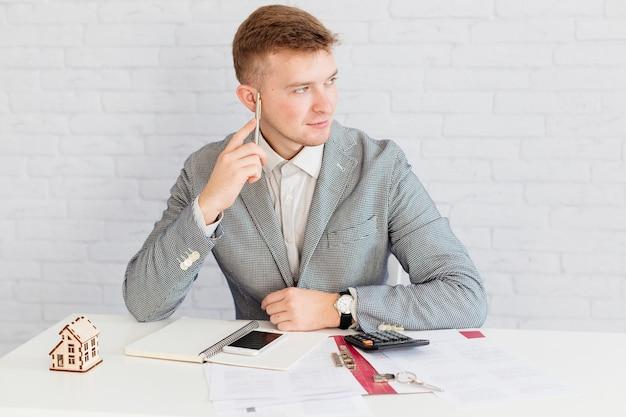 Corretor de imóveis pensativo sentado no escritório