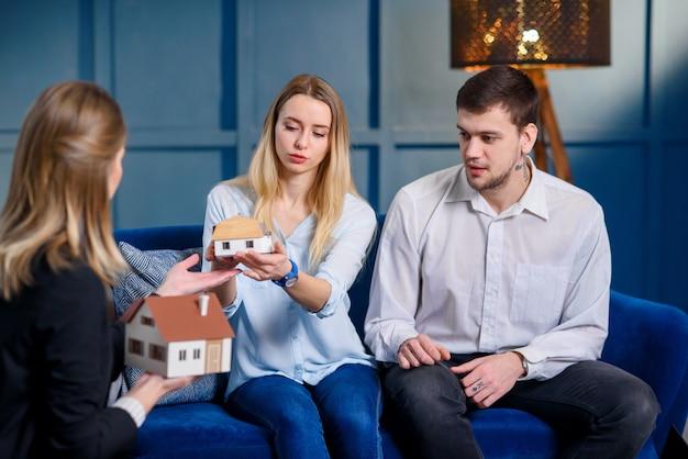 Corretor de imóveis profissional, designer de interiores, decorador, discutindo o projeto com o jovem casal elegante.