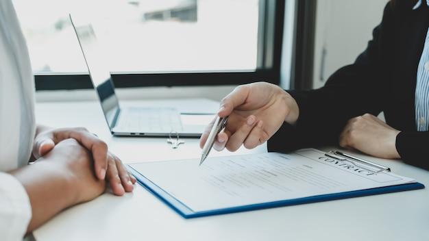 Corretor de imóveis segurando uma caneta e explicando o contrato de negócios ou seguro residencial
