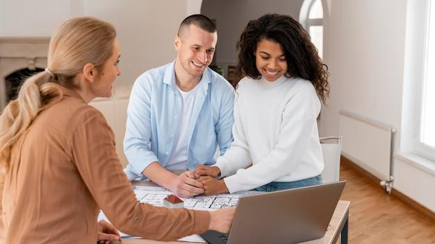 Corretor de imóveis sorridente mostrando nova casa para casal no laptop