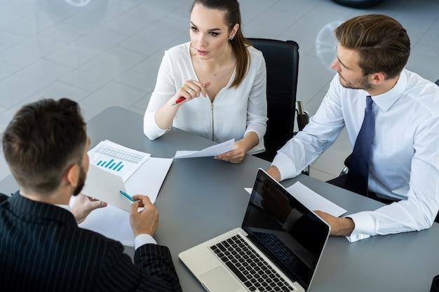 Corretor de seguros ou vendedor, fazendo oferta ao jovem casal milenar usando laptop no café, corretor de imóveis, consultoria de clientes sobre hipoteca sentado à mesa de café, apontando na tela do computador.