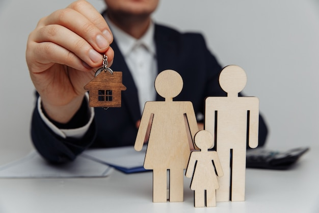 Corretor detém as chaves de uma casa para um jovem conceito de hipoteca familiar