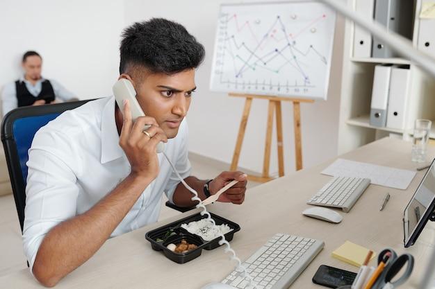 Corretor do mercado de ações almoçando em sua mesa de escritório e atendendo a ligação de um cliente