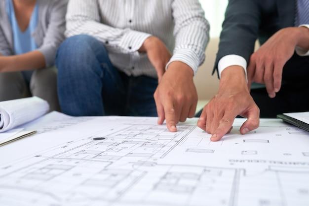 Corretor e clientes discutindo blueprint