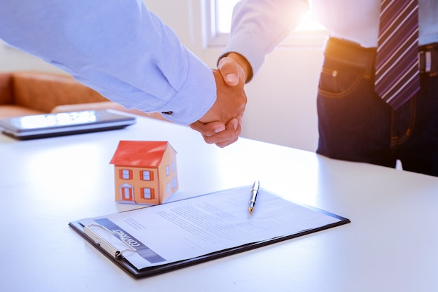 Corretor imobiliário e cliente apertando as mãos depois de assinar um contrato.