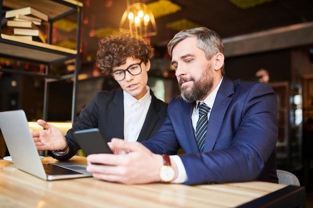 Corretor ou comerciante confiante em trajes formais mostrando a jovem empresária algo em seu smartphone
